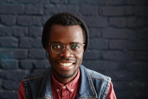 Indoor portret van gelukkige en vrolijke jonge donkere mannelijke student trendy kleding dragen