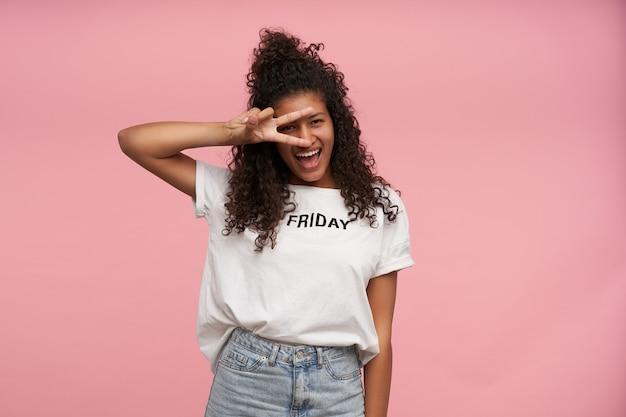 Indoor portret van gelukkige jonge brunette donkere huid vrouw met lang krullend haar gekleed in wit t-shirt en spijkerbroek poseren op roze, vredesgebaar naar haar gezicht verhogen en vreugdevol glimlachen