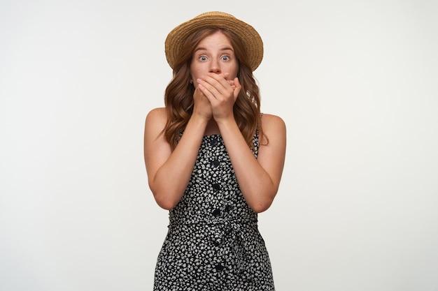 Indoor portret van geschokt jonge mooie roodharige vrouw poseren, versuft kijken en mond sluiten met gekruiste handpalmen