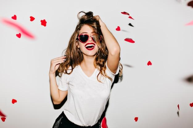 Indoor portret van geweldig vrouwelijk model in trendy t-shirt aan haar lange glanzende haren te raken