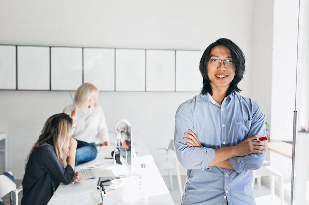 Indoor portret van internationale medewerkers met lachende aziatische man op voorgrond