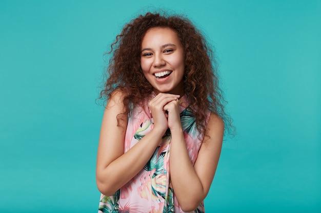 Indoor portret van jonge blije bruinharige krullende dame die gevouwen handen onder haar kin houdt terwijl ze vrolijk kijkt, staande op blauw