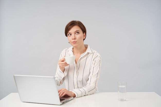 Indoor portret van jonge bruinharige vrouw gekleed in formele kleding kopje koffie in opgeheven hand houden en bedachtzaam naar boven kijken, poseren op wit