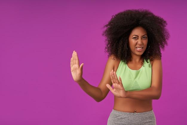 Indoor portret van jonge gekrulde vrouw met donkere huid dragen casual kapsel, fronsen haar gezicht en raspende handpalmen in weigering gebaar, staande op paars
