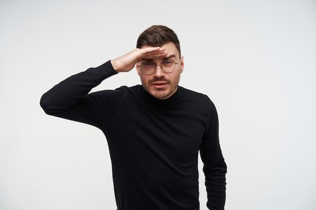Indoor portret van jonge knappe bebaarde brunette man zijn ogen loensen en houden de wijsvinger op het voorhoofd terwijl vooruitkijkend, die zich voordeed op wit