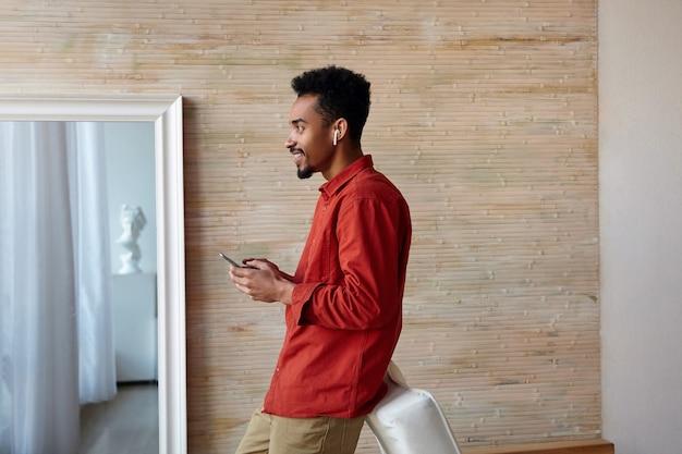 Indoor portret van jonge kortharige bebaarde donkere huid man mobiele telefoon in opgeheven handen houden en cheeeful vooruit kijken, staande op beige interieur