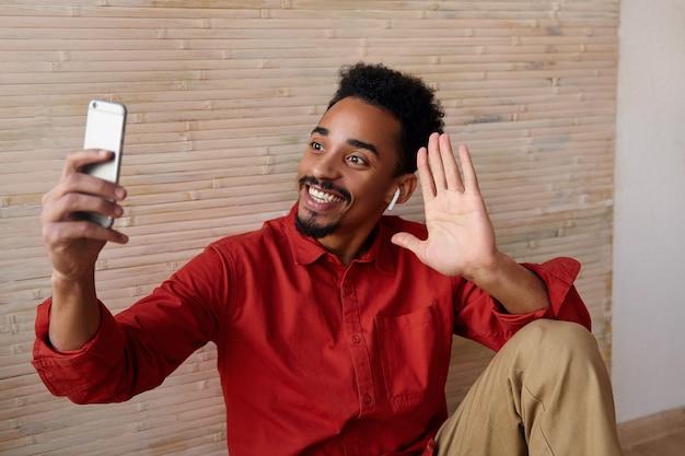 Indoor portret van jonge kortharige bebaarde man met donkere huid hand opsteken hallo gebaar en vrolijk glimlachen tijdens het maken van videogesprek, geïsoleerd op interieur