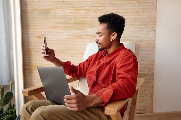 Indoor portret van jonge kortharige bebaarde man met donkere huid terwijl hij zijn hand omhoog houdt terwijl hij smartphone vasthoudt tijdens videogesprek, zittend op het interieur