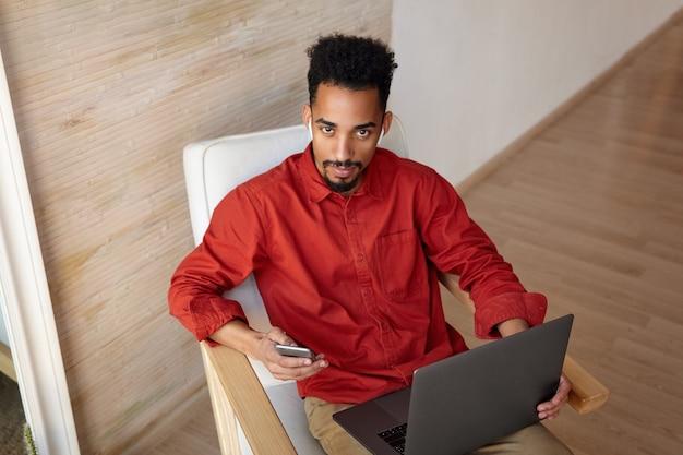 Indoor portret van jonge kortharige bebaarde man met donkere huid werken met zijn laptop en smartphone zittend in een stoel op interieur in casual kleding