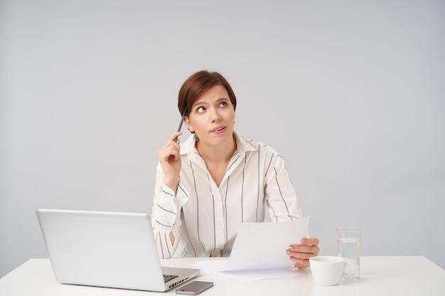 Indoor portret van jonge kortharige brunette vrouwelijke werknemer die stuk papier houdt en bedachtzaam naar boven kijkt, documenten voorbereidt voor aanstaande vergadering, geïsoleerd op wit