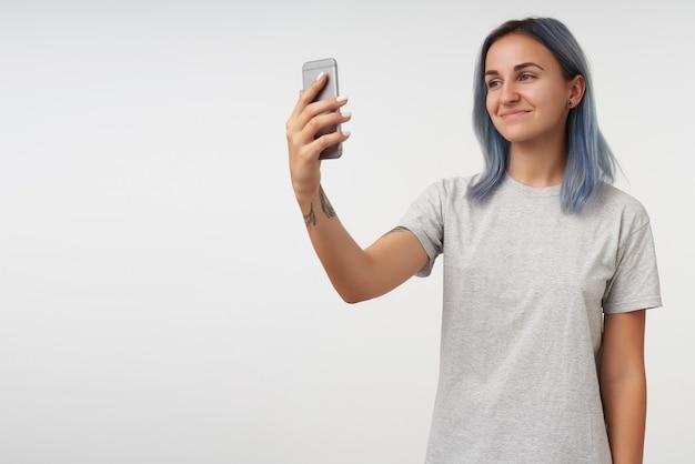Indoor portret van jonge kortharige positieve getatoeëerde vrouw mobiele telefoon in opgeheven hand houden en aangenaam glimlachen, geïsoleerd op wit