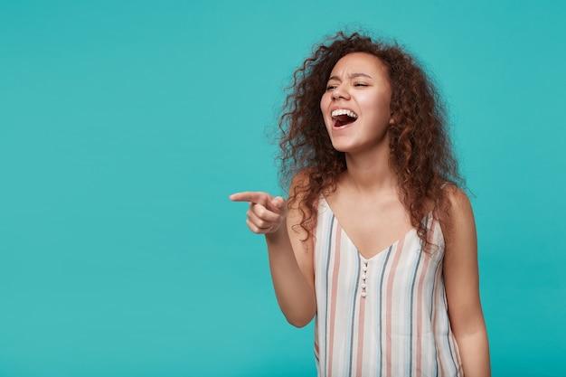 Indoor portret van jonge opgewonden krullende brunette vrouw gekleed in gestreepte top opgewonden vooruit kijken terwijl het tonen met wijsvinger, geïsoleerd op blauw