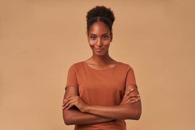 Indoor portret van jonge positieve krullende brunette dame met donkere huid haar handen op de borst vouwen en lichtjes glimlachen, staande op beige