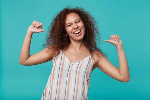 Indoor portret van jonge vrij langharige krullende dame met casual kapsel wijzend op zichzelf met duimen terwijl vreugdevol kijken, geïsoleerd op blauw