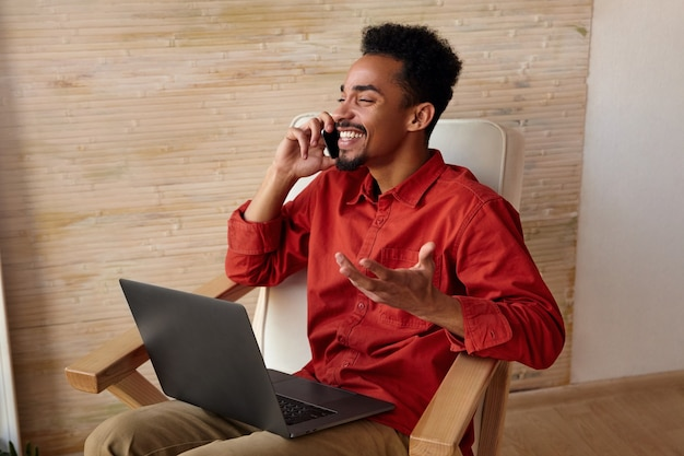 Indoor portret van jonge vrolijke bebaarde donkere huid man met kort kapsel lachen gelukkig met gesloten ogen terwijl telefoon praten, geïsoleerd op beige interieur