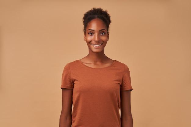 Indoor portret van jonge vrolijke bruinharige gekrulde vrouw met donkere huid glimlachend vrolijk terwijl staande op beige met handen naar beneden