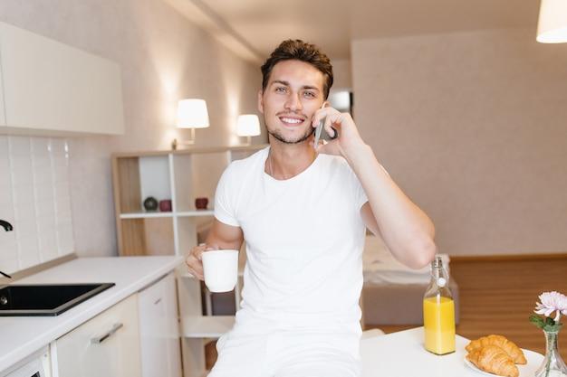 Indoor portret van lachende drukke man praten over de telefoon tijdens het ontbijt