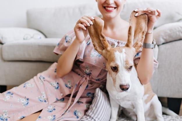 Indoor portret van lachende vrouw in romantische roze jurk met schattige beagle puppy op voorgrond. geweldig meisje met witte manicure spelen met de oren van de hond en lachen