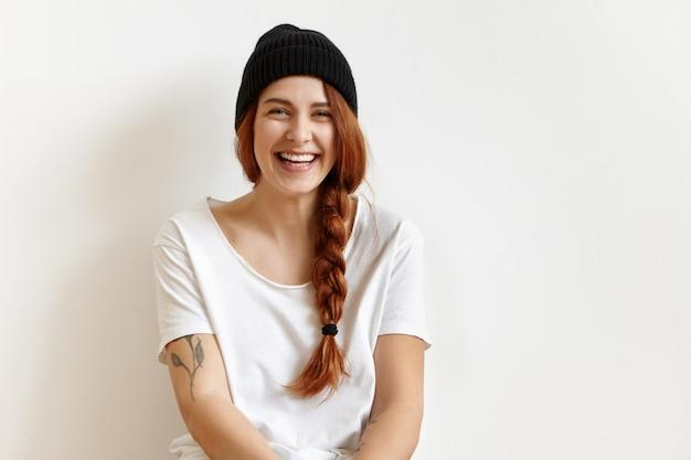 Indoor portret van modieuze en vrolijke jonge vrouw met vlecht