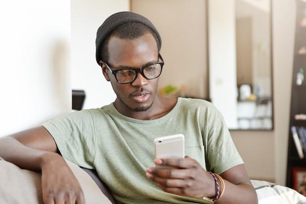 Indoor portret van modieuze jonge afro-amerikaanse man met rust thuis, zittend op de bank met touchscreen mobiele telefoon, met behulp van online app