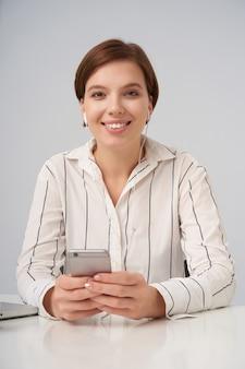 Indoor portret van mooie jonge bruinogige brunette vrouw op zoek positief met charmante glimlach, zittend op wit met smartphone in haar handen