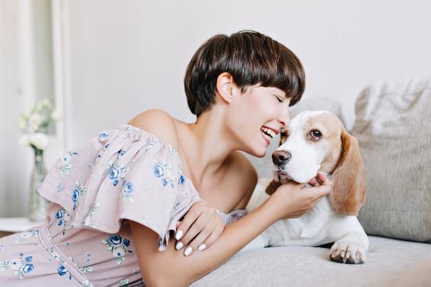 Indoor portret van opgewonden jonge vrouw met glanzend donkerbruin haar krassen tevreden beagle hond met glimlach