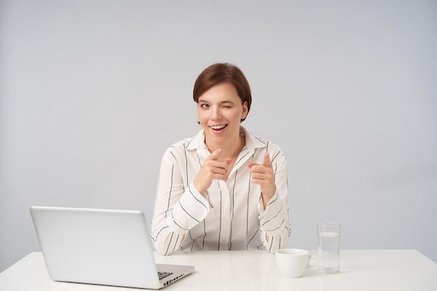 Indoor portret van positieve jonge bruinharige dame met natuurlijke make-up vrolijk knipogen en opzij wijzend met opgeheven wijsvingers, zittend op wit