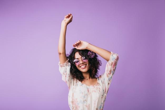 Indoor portret van prachtige afrikaanse vrouw opstaan met handen omhoog. vrouwelijk model met golvend haar dat goede emoties uitdrukt.