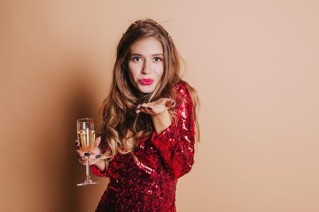Indoor portret van schattige europese vrouw in rode jurk lucht kus verzenden en glas champagne te houden