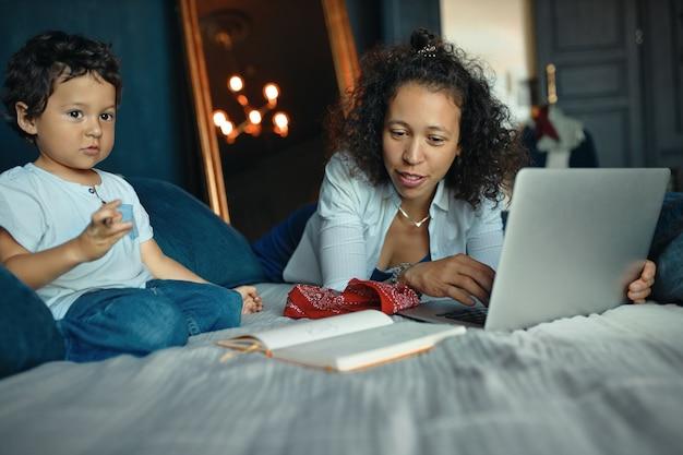 Indoor portret van schattige gemengd ras kleine jongen zittend op bed en het maken van tekeningen terwijl zijn jonge moeder met behulp van draagbare computer voor extern werk.