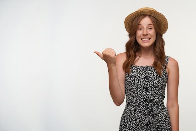 Indoor portret van schattige positieve jonge vrouw in romantische jurk en strooien hoed, breed glimlachend en opzij wijzend met duim, poseren