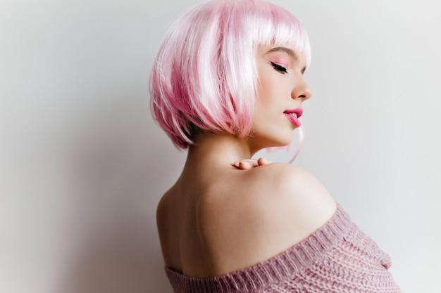 Indoor portret van sierlijke witte vrouw poseren met plezier foto van mooi meisje in roze peruke dromen over iets.