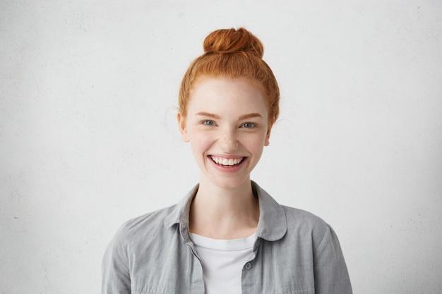Indoor portret van stijlvolle teenag meisje met sproeten en rood haar broodje camera kijken met vrolijke glimlach