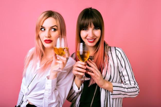 Indoor portret van twee gelukkige beste vrienden zusters vrouwen, trendy zwart-witte kleren dragen, gewaardeerd gezicht aanklagen