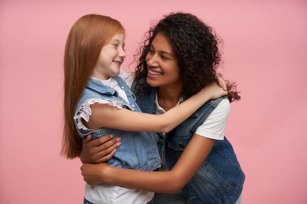 Indoor portret van twee vrolijke jonge meisjes die liefdevol naar elkaar kijken en oprecht glimlachen, zachte knuffels geven en leuke tijd samen hebben, geïsoleerd op roze
