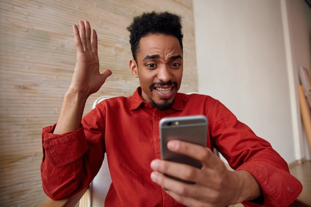 Indoor portret van verbijsterde jonge bebaarde donkere huid man kijken opgewonden naar het scherm van zijn mobiele telefoon en houden de hand omhoog, geïsoleerd op interieur