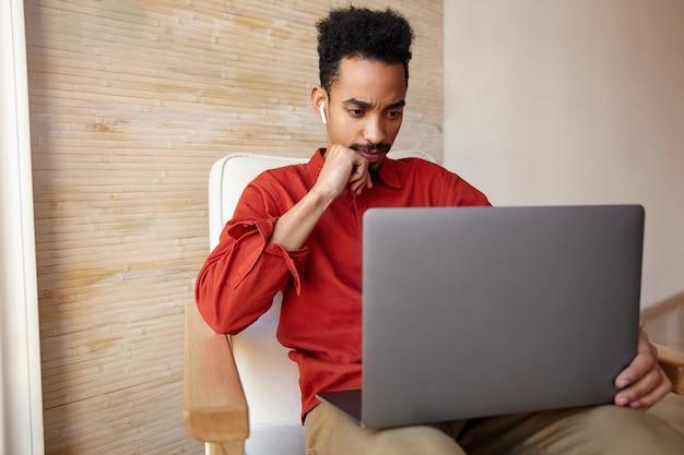 Indoor portret van verwarde jonge kortharige brunette man met donkere huid, zijn kin leunend op opgeheven hand en fronsende wenkbrauwen terwijl hij naar het scherm van zijn laptop kijkt