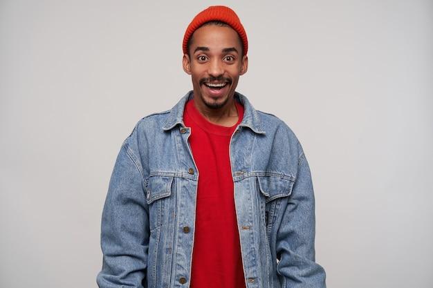 Indoor portret van vrolijke jonge bruinogige, bebaarde donkere man met een donkere huid die gelukkig kijkt met een brede glimlach, in een hoge geest terwijl hij op wit staat