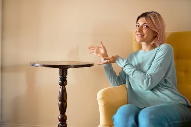 Indoor portret van vrolijke jonge europese vrouw met roze haren, zittend op een comfortabele bank naast ronde tafel