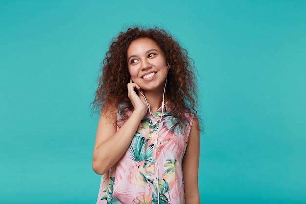 Indoor portret van vrolijke jonge krullende brunette vrouw met natuurlijke make-up opzij kijken met charmante glimlach tijdens het luisteren naar muziek met koptelefoon, geïsoleerd op blauw