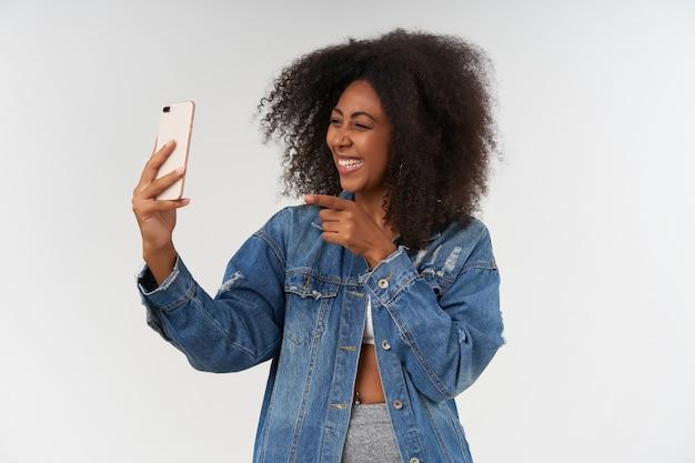 Indoor portret van vrolijke jonge krullende donkere vrouw in casual kleding met smartphone in opgeheven hand, prettig praten met videochat, gelukkig glimlachend over witte muur