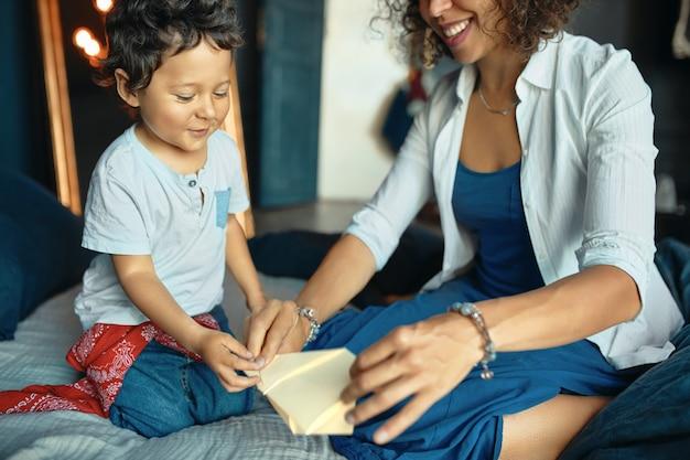 Indoor portret van vrolijke opgewonden kleine jongen zittend op bed met zijn jonge moeder speelgoed vliegtuig maken