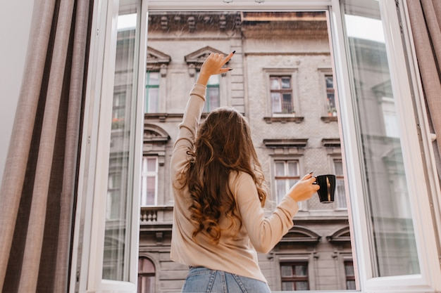 Indoor portret vanaf achterkant slank meisje met lang krullend haar draagt jeans