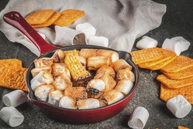 Indoor sâ € ™ mores, gebakken sâ € ™ mores dip in een gietijzeren koekenpan met graham crackers., donkergrijze tafel, copyspace