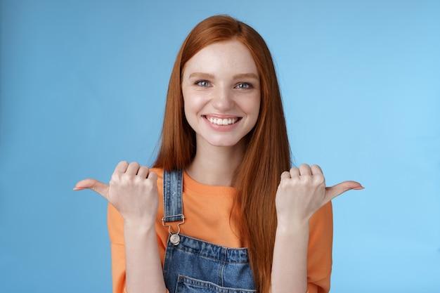 Indoor shot charismatisch assertief blij lachend roodharige vrouw oranje overhemd denim overall wijzend zijwaarts duimen links rechts tonen keuzes kansen geven kans kiezen blauwe achtergrond