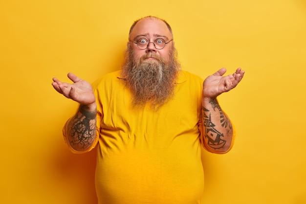 Indoor shot van aarzelende bebaarde man met overgewicht haalt zijn schouders op en staat onbewust, heeft dikke baard, grote bierbuik, gekleed in geel t-shirt, ronde bril, gezichten moeilijke keuze.