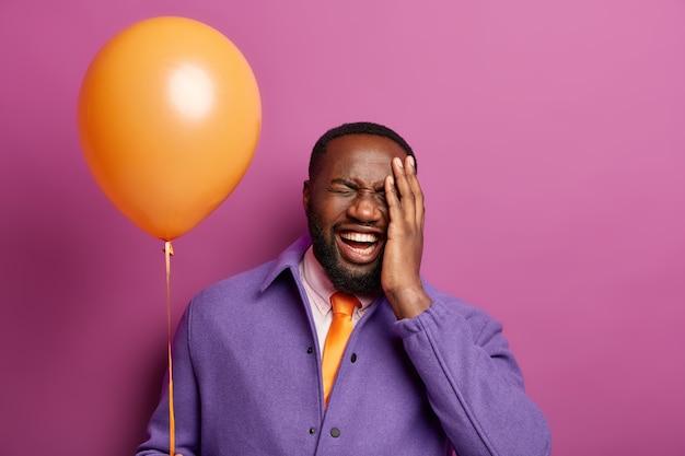 Indoor shot van afro-amerikaanse dolgelukkig man lacht vrolijk, drukt vreugde en geluk uit, houdt ballon vast, bedekt gezicht met palm