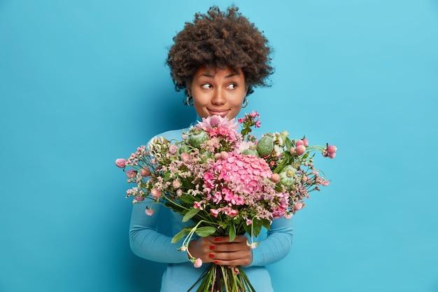 Indoor shot van afro-amerikaanse vrouw ontvangt mooie bloemen geniet van romantische date looks met dromerige peinzende uitdrukking opzij krijgt boeket van geheime bewonderaar of minnaar geïsoleerd op blauwe studio muur