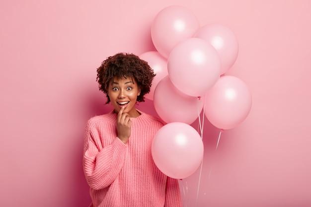 Indoor shot van blije optimistische jonge afro-amerikaan verrast om aanwezig te zijn, houdt luchtballonnen vast, draagt een oversized trui, houdt de vinger op de onderlip, tevreden om aanwezig te zijn op feestviering.