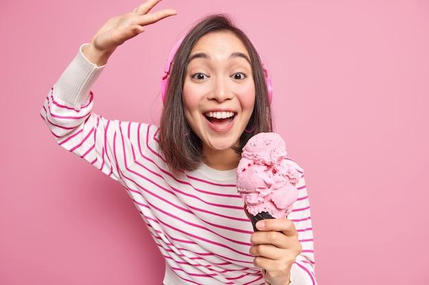 Indoor shot van brunette vrouw met oosterse uitstraling danst zorgeloos tilt arm glimlacht graag eet heerlijk ijs luistert muziek draagt casual gestreepte trui geïsoleerd over roze muur.